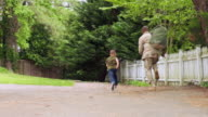 African American military father running on path with son