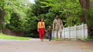 African American military father walking with wife and son