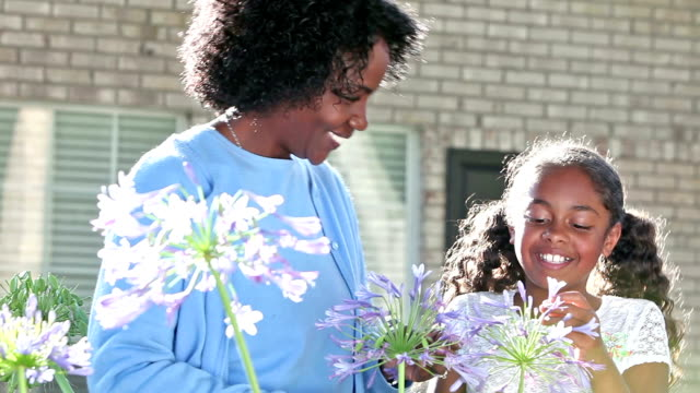 African American mother and daughter hugging in garden