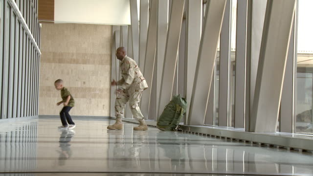 African American soldier and son dancing in airport