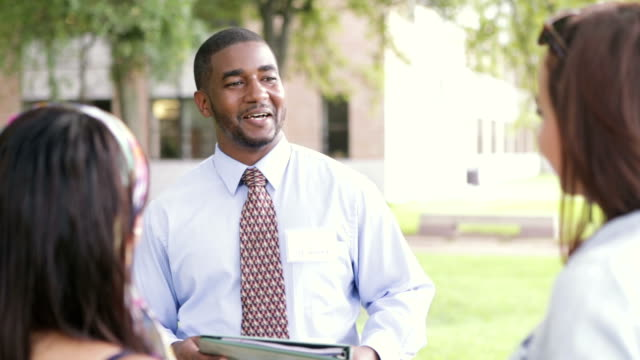 African American tour guide showing students around college campus