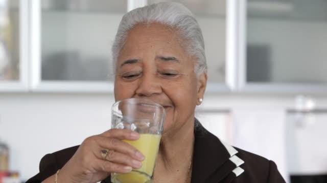 African American woman drinking orange juice