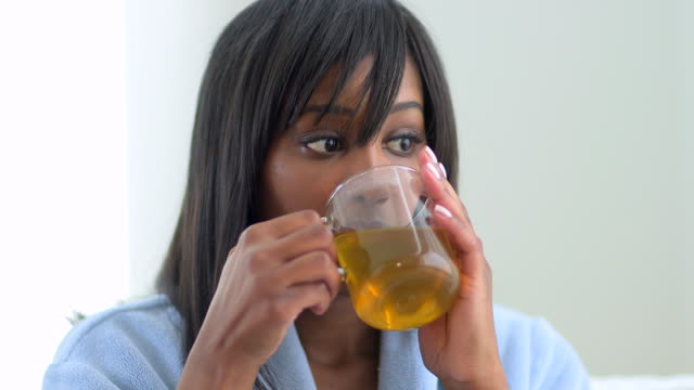 African American woman drinking tea in robe