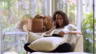 African American woman reading book and talking on cell phone