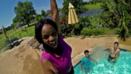 African American young woman smiles while diving into backyard swimming pool
