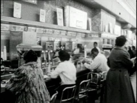 African Americans eat with caucasians at a Woolworth's lunch counter after the overturning of segregation laws