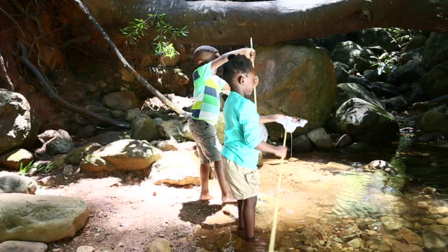 African brother and sister fishing with nets in a pond