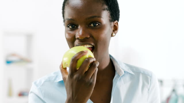 HD: African Businesswoman Eating Apple