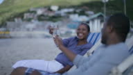 African couple on the beach drinking wine