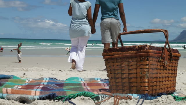 African couple walking on the beach, holding hands