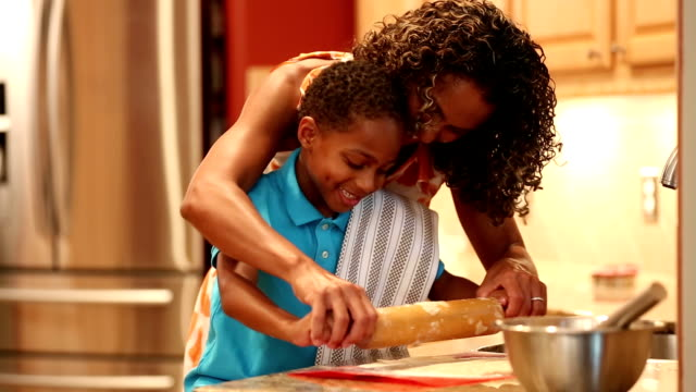 African descent mother teaches son how to make cookie dough.