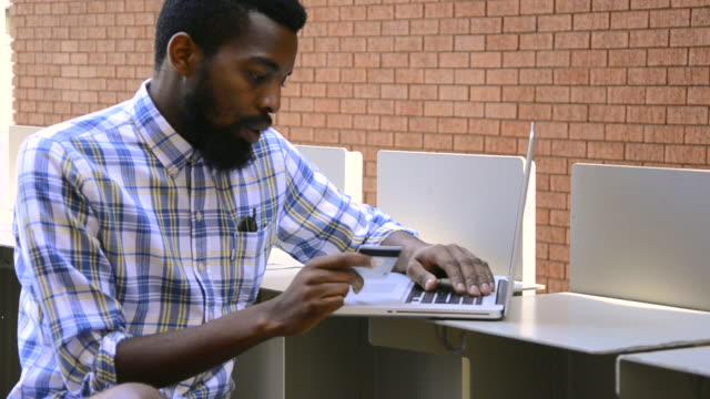 MS of African Ethnicity man using laptop to make credit card payment / Johannesburg, Gauteng, South Africa
