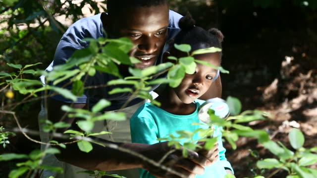 African father and daughter exploring plants