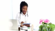 African Female doctor at her desk with new technology