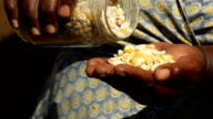 African female farmer pouring out beans from jar, KwaZulu Natal, South Africa