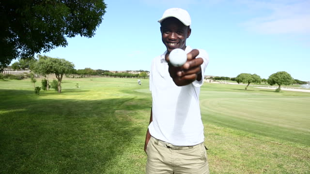 African golfer showing his golf ball to the camera