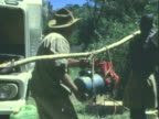 MS African indigenous peoples carrying power generator suspended from wood pole / Africa