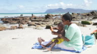African mother and son at the beach, putting sunblock on