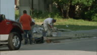 HD AfricanAmerican Black teen young boy riding bicycles on sidewalk passing behind truck workers cleaning up blighted neighborhood on rebound...