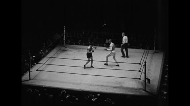 AfricanAmerican boxer Mark Hough wins round in the 160lb class exits boxing ring / VS boxers Gino Rossi of Italy and Dick Madden of the US as they...