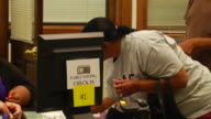 AfricanAmerican citizens check in at the early voting registrars office