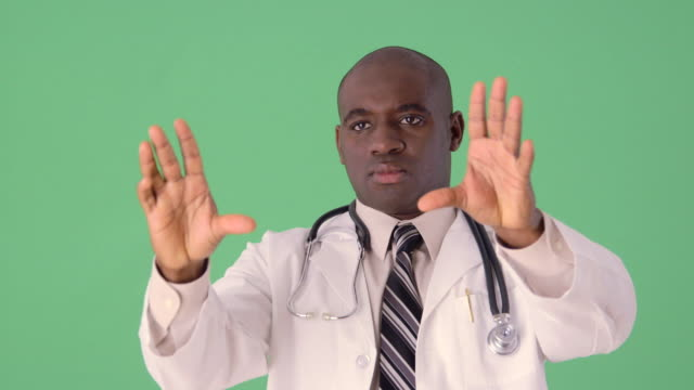 African-American Doctor using touch screen and futuristic display