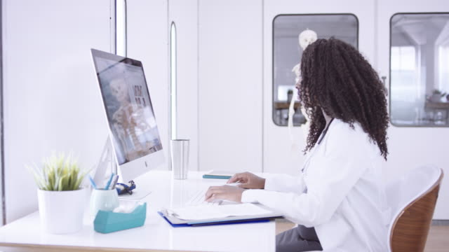4K UHD: African-American doctor working at computer