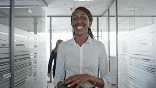African-American weiblichen Büroangestellten lächelnd als She-Spaziergänge durch den Flur Büro