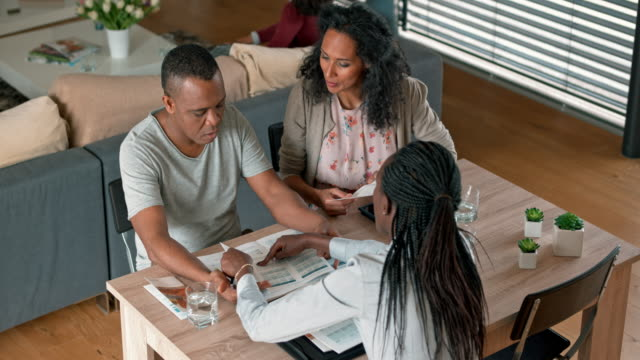 African-American insurance agent advising a multi ethnic couple in their home