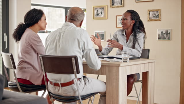 African-American insurance agent consulting a senior couple in their home