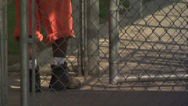 AfricanAmerican male inmate legs in rolled up prison pants high top sneakers socks closing outer gate walking to opening inner gate walking sidewalk...