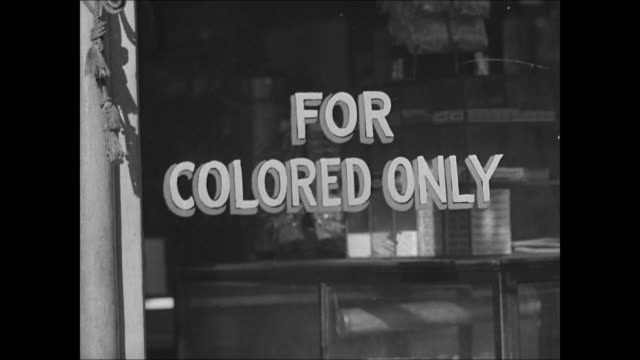 AfricanAmerican man crossing street cars shops BG MS 'Booker T Luncheon' CU Sign 'For Colored Only' WS NegroAmericans on city streets WS...