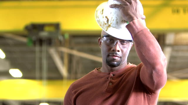 Afrikanisch-amerikanischer Mann im Lager setzt auf Bauarbeiterhelm