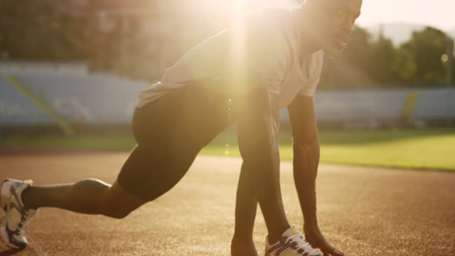 SLO MO African-American man stretching in the stadium on the track in setting sun