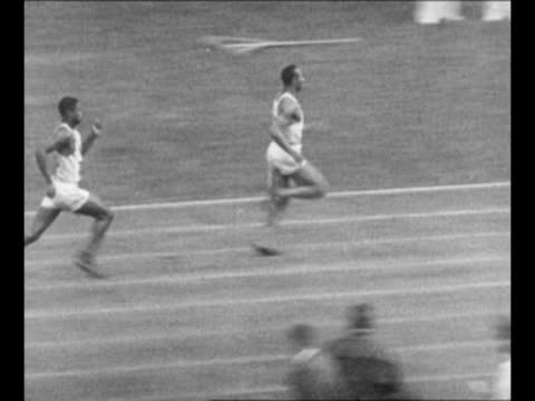 AfricanAmerican olympian Jesse Owens stands in US track uniform smiles / Owens wins men's sprint race / Owens does long jump and white athlete...
