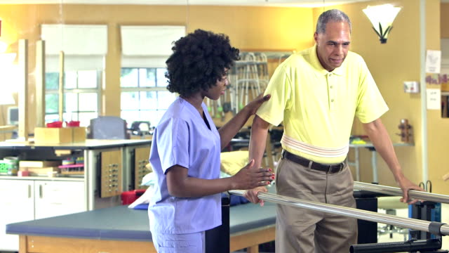 African-American physical therapist helping patient