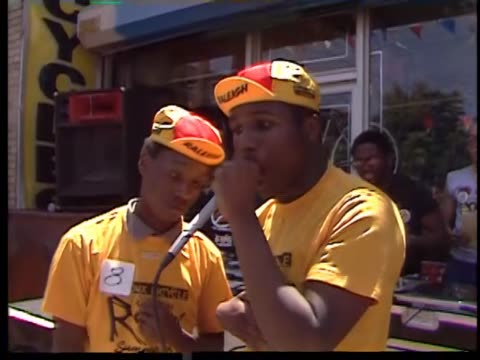 AfricanAmerican Teen raper and a human beat boxer both perform in front of applauding crowd on city street