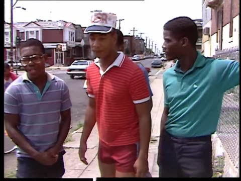 4 AfricanAmerican teenage boys rapping with human beat boxer on a sidewalk
