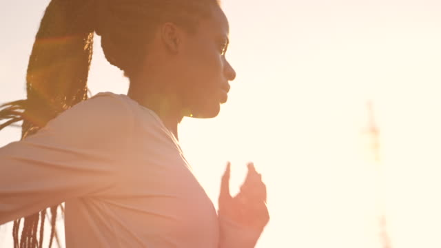 SLO MO TS African-American woman with braided hair running at sunset