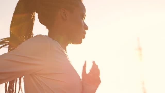 SLO MO TS Afroamerikanerin mit geflochtenen Haaren laufen bei Sonnenuntergang