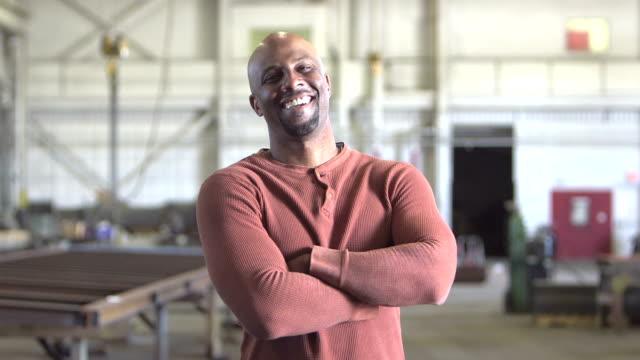Afroamerikanische Arbeiter in Fabrik, geht bis zu Kamera