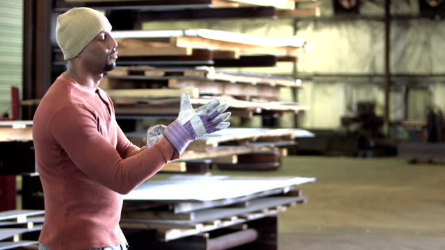 Afroamerikanische Arbeiter Schutzhandschuhe anziehen