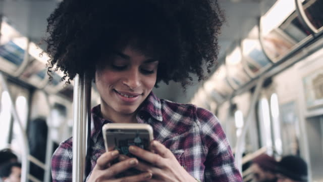 Afro American Female on subway with smart phone