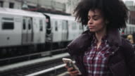 Afro American Female standing on train platform with mobile phone