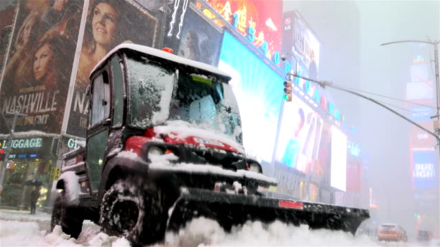 After a day of 60 degree Fahrenheit temperature winter storm Niko hits the Northeast of the United States / Utility vehicle plowing cleaning snow...