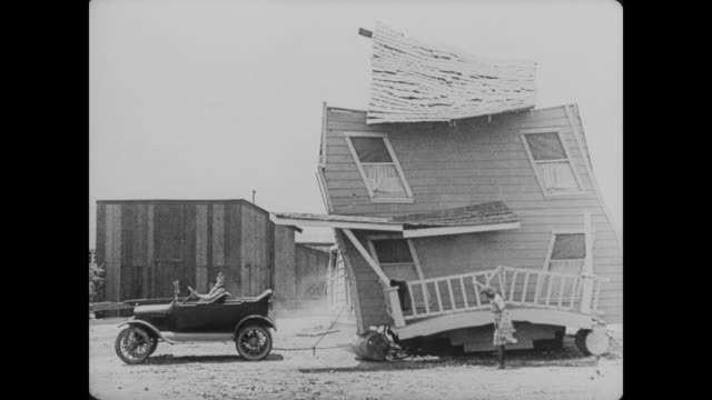 After learning that they built their house on the wrong lot, Buster Keaton and his wife place the house on barrels and pull it behind their car