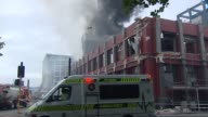 Aftermath with smoke rising from site of badly damaged CTV building and police and St John Ambulance staff assisting injured victims in temporary...