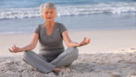 WS Aged woman doing yoga sitting on beach / Cape Town, Western Cape, South Africa