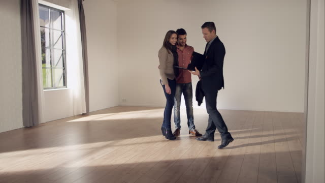 Agent presenting new apartment to young couple