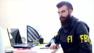 FBI agent with a beard working in his office